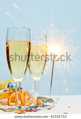 Two glasses of champagne with ribbons and burning sparkler