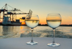 two glasses of cool white wine on white tablecloth with harbor structures and cargo ship in blurred background at sunset