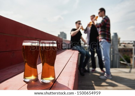 Two glasses of draft beer and  male friends in blur drinking beer at outdoor pub on background, copy space, copy space. Friendship and celebration concept