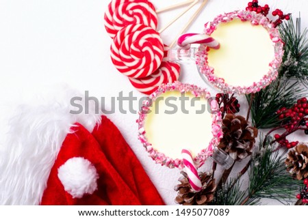Two glasses of eggnog with candy cane, santa hat and christmas tree on white background. Top view. #1495077089