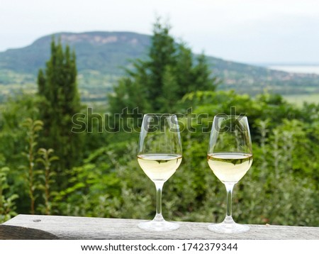 Two glasses of fine riesling wine in the Badacsony region in Hungary with volcanic hill Badacsony in the background Stock photo ©