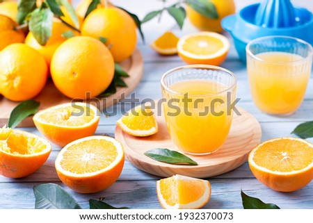 Two glasses of fresh juice, fruit squeezer and ripe fresh oranges on blue wooden table top, fresh orange juice making, top view