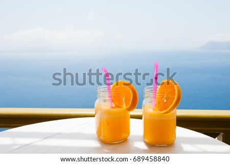 Two glasses of fresh orange juice on the table, blue sea background