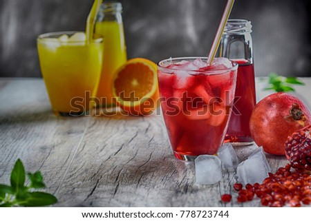 Two glasses of freshly pressed juice on a wooden table. So there are fresh orange, and fresh pomegranate near. Selective focus. #778723744