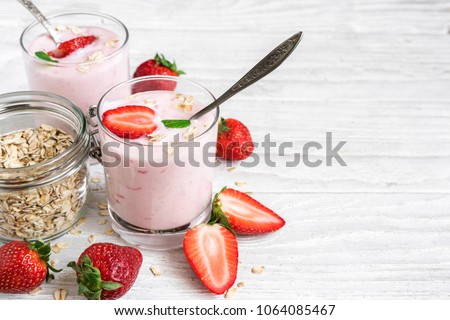 two glasses of healthy strawberry yogurt with fresh berries, oats spoon and mint on white wooden table. healthy breakfast. close up with copy space #1064085467