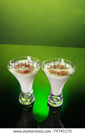 Two glasses of holiday egg nog decorated with kiss like cinnamon topping