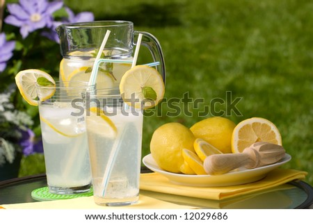 Two glasses of home made iced cold lemonade and pitcher on hot summer. Copyspace - stock photo