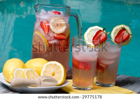 Two glasses of home made iced cold pink strawberry lemonade and pitcher on hot summer on edge of swimming pool. - stock photo