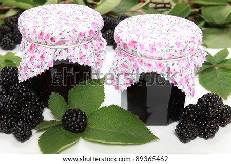 Two glasses of homemade blackberry jam with fresh fruits  and leaves