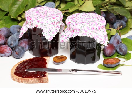 Two glasses of homemade damson jam with fresh fruits and leaves