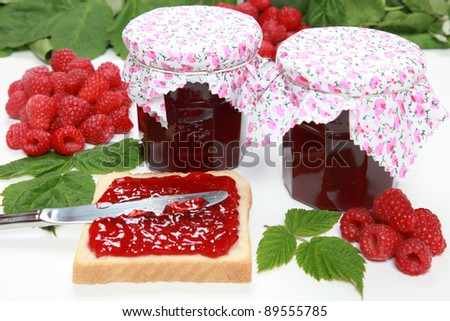 Two glasses of homemade raspberry jam with fresh fruits, toast and leaves