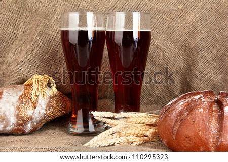 two glasses of kvass with bread on canvas background close-up - stock photo