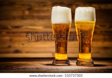 Two glasses of lager served on old wooden planks, copyspace for text