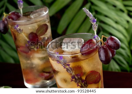 Two glasses of lavender and grapes iced tea garnished with lavender twig on a table in a restaurant on a tropical beach.