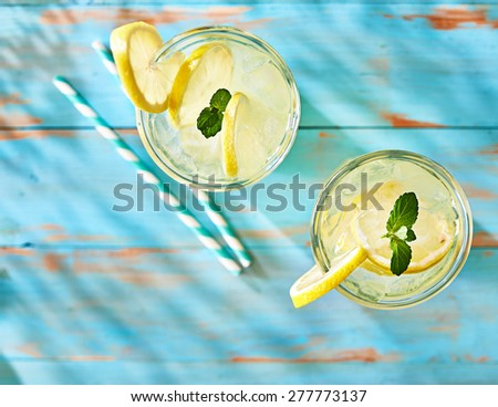 two glasses of lemonade shot from overhead view on rustic table top