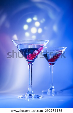 Two glasses of martini cocktail with red cherries on a mixed color background.