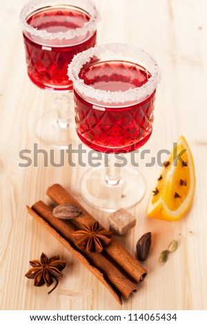 Two glasses of mulled wine and spices: cinnamon, cloves, cardamom