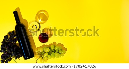 Photo of Two glasses of red and white wine, a bottle, grapes on a yellow background. The concept of Italian wine. Photo with hard shadows, top view. Banner, long format. Free space for text
