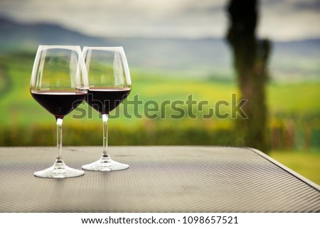 two glasses of red wine against beautiful landscape in Tuscany #1098657521