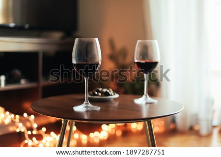 Two glasses of red wine and olives on a table, cosy room with candid lights, concept of romantic evening Stock fotó ©