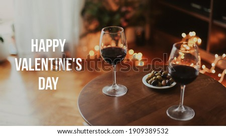 Two glasses of red wine at home, cosy lights, romantic atmosphere. Banner with title in English 'HAPPY VALENTINES DAY'. Spending a romantic evening at home Stock fotó ©