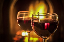 Two glasses of red wine beside the fire.