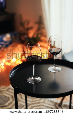 Two glasses of red wine on a black little table, cosy living room with candid Christmas lights  Stock fotó ©