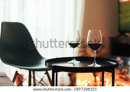 Two glasses of red wine on a table, cosy room with candid lights, chairs, carpet and a tv Stock fotó ©