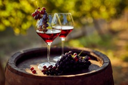 Two glasses of red wine with a bottle on a wooden barrel