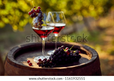 Two glasses of red wine with a bottle on a wooden barrel #1161932551