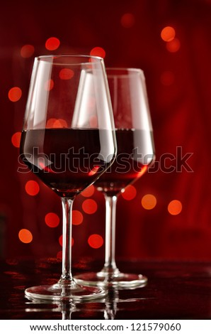 Two glasses of red wine with celebratory lights