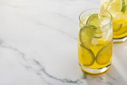 Two glasses of refreshing lemonade with lime and lemon. Copy space, marble background.