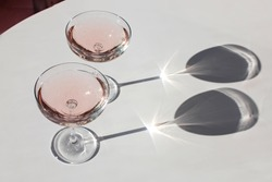Two glasses of rose sparkling wine on the pink table in natural sunlight with shadows. Minimalist creative composition