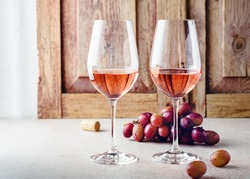Two glasses of rose wine and a bunch of grapes on a light wooden background.
