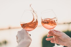 Two glasses of rose wine in hands against the sunset sky.