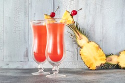Two glasses of Singapore Sling on wooden background
