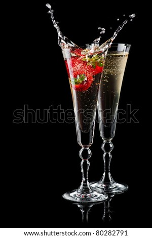 Two glasses of sparkling wine (champagne) with splash and strawberry on black
