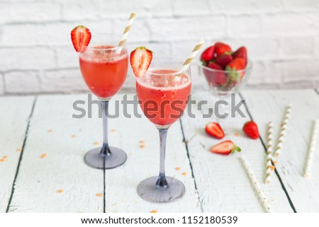 Two glasses of sparkling wine cocktail with strawberry sorbet. New years eve celebration. Wineglasses with champagne and gold paper straws for wedding party Stock photo ©
