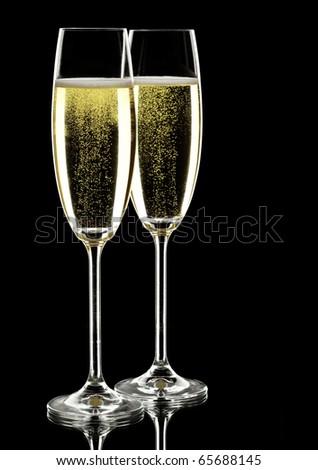 two glasses of sparkling wine, over black, studio shot - stock photo