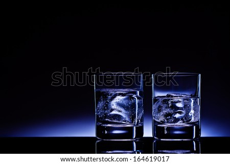 Two glasses of vodka with ice cubes against the background of deep blue glow.