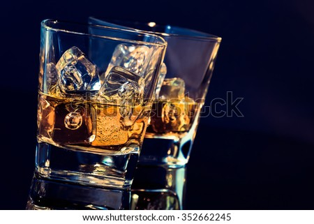 two glasses of whiskey with ice cubes on black background with light tint blue and reflection, time of relax with whisky