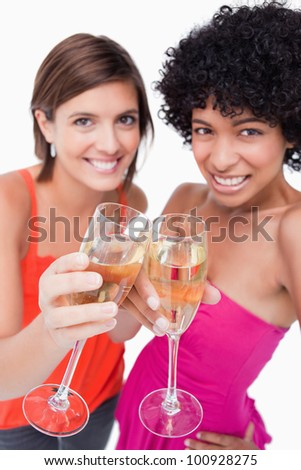Two glasses of white wine being clinked by young women