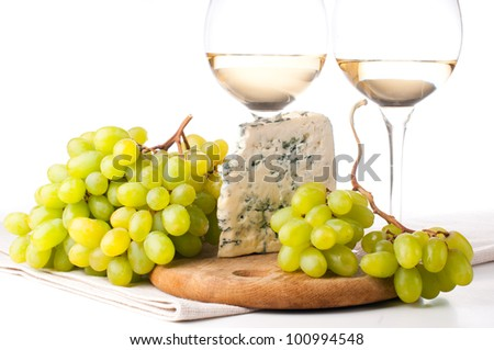 Two glasses of white wine, blue cheese and a bunch of white grapes on white background