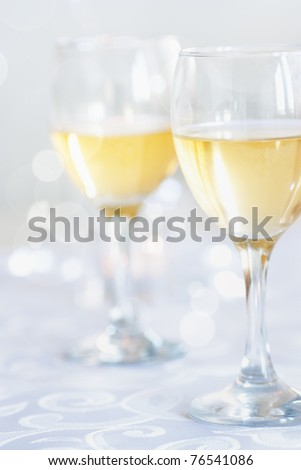 Two glasses of white wine on festive tablecloth