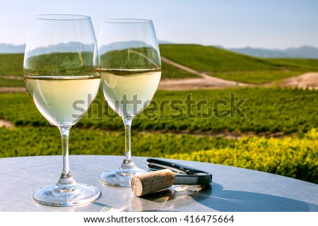 two glasses of white wine on table overlooking California wine country on sunny, cloudless day