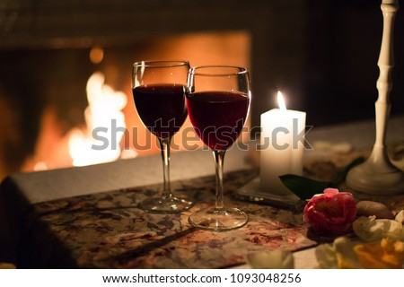 Two glasses of wine against the fireplace with fire on the table set for a romantic dinner for two in restaurant. #1093048256