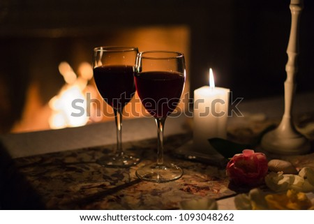 Two glasses of wine against the fireplace with fire on the table set for a romantic dinner for two in restaurant. #1093048262