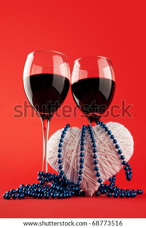 Two glasses of wine and a heart on a red background. Valentine's Day