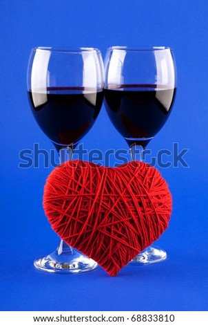 Two glasses of wine and a red heart on a blue background - stock photo