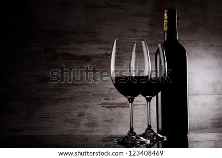 two glasses of wine and bottle over grunge background